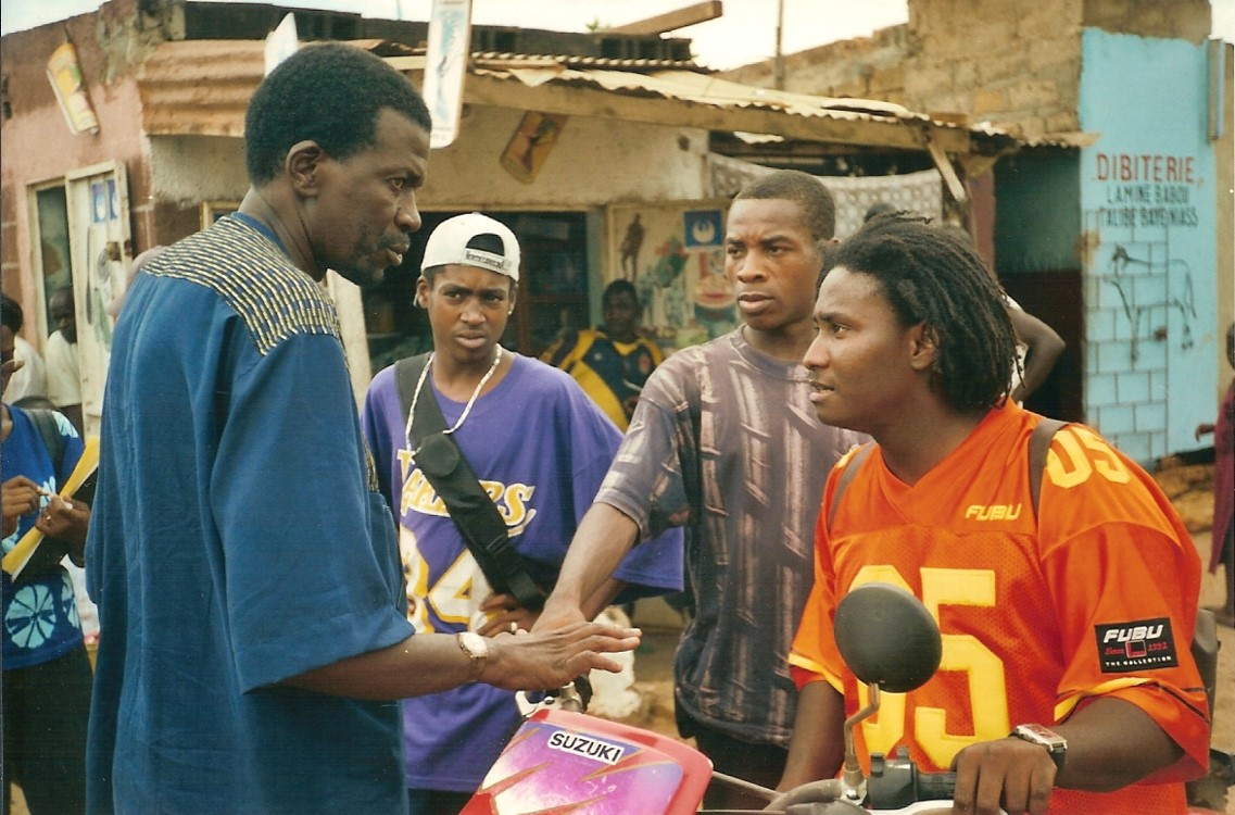 Celebrated Malian filmmaker Cheick Oumar Sissoko (left) directed rapper/actor Didier Awadi (in orange)